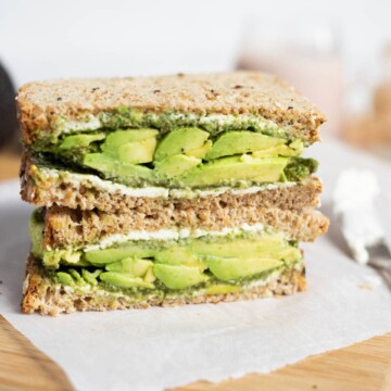 Sandwich with avocado, chutney and cream cheese on a cutting board