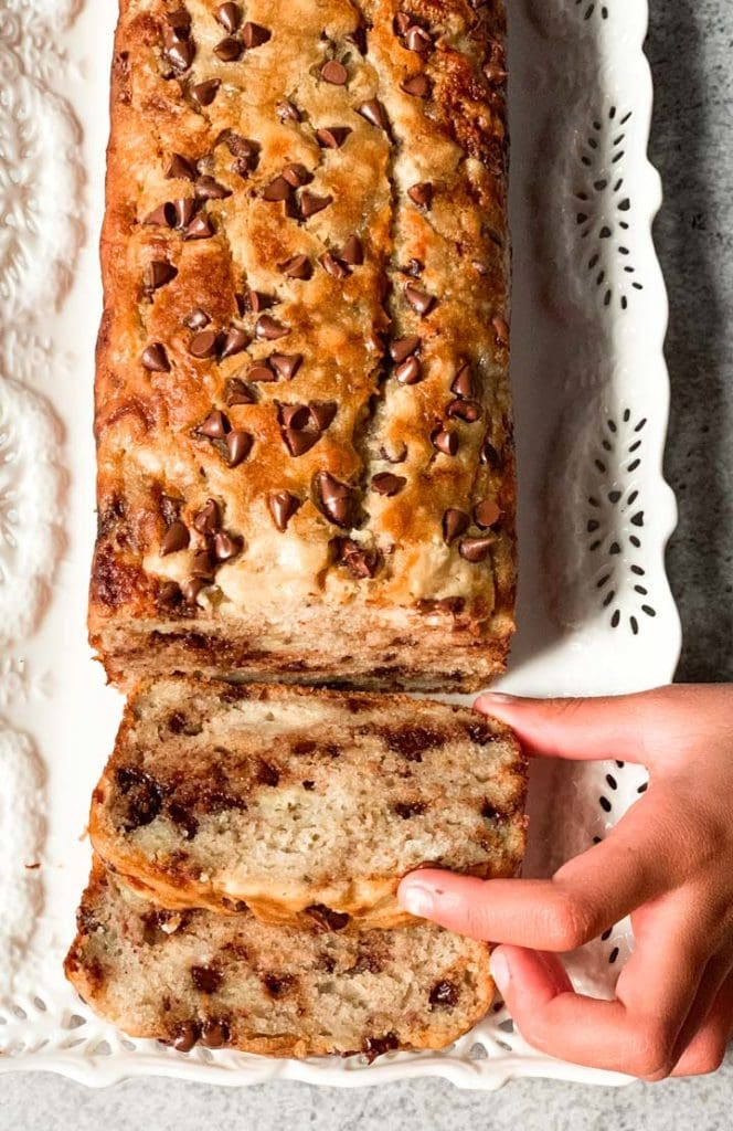 Kid hands picking a slice of banana chocolate chip bread