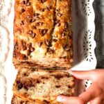 Banana Bread with chocolate chip slice being taken by hand
