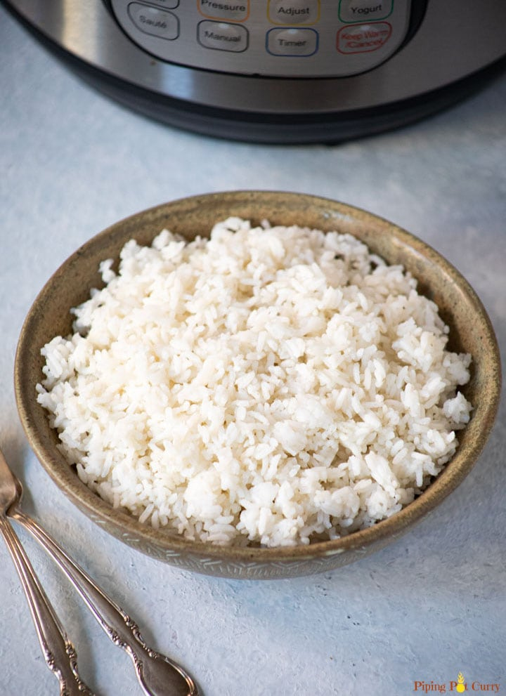 White sona masoori rice in a bowl in front of the instant pot