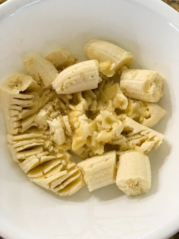 Bananas in a white bowl being mashed