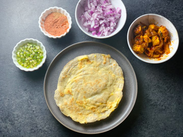 All ingredients ready around a flatbread roti to make a Frankie