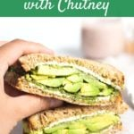 Avocado Sandwich with chutney being picked to eat