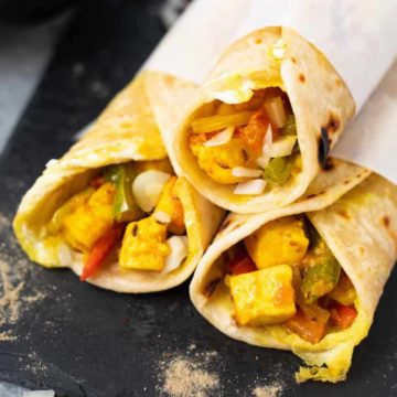 Three paneer Kathi roll wraps on a black base
