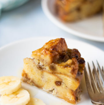 bread pudding drizzled with syrup and sliced banana on the side.