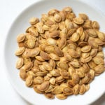 Seasoned roasted pumpkin seeds in a white plate