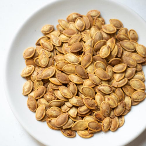 Seasoned roasted pumpkin seeds in a white plate
