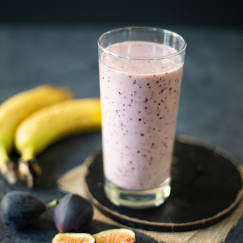 Fig Banana Smoothie in a glass with the ingredients around the glass