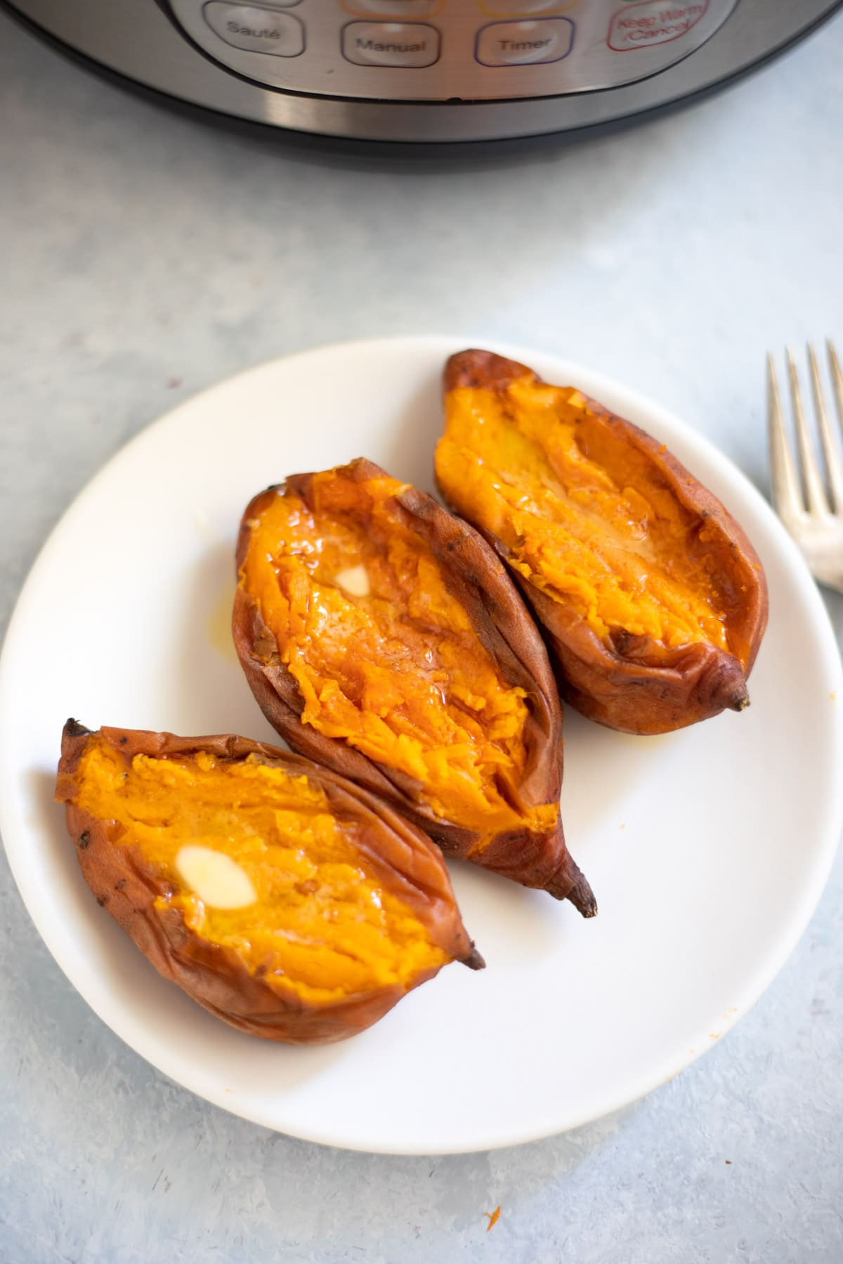 Three Creamy buttery Sweet potatoes in a plate in front of the instant pot