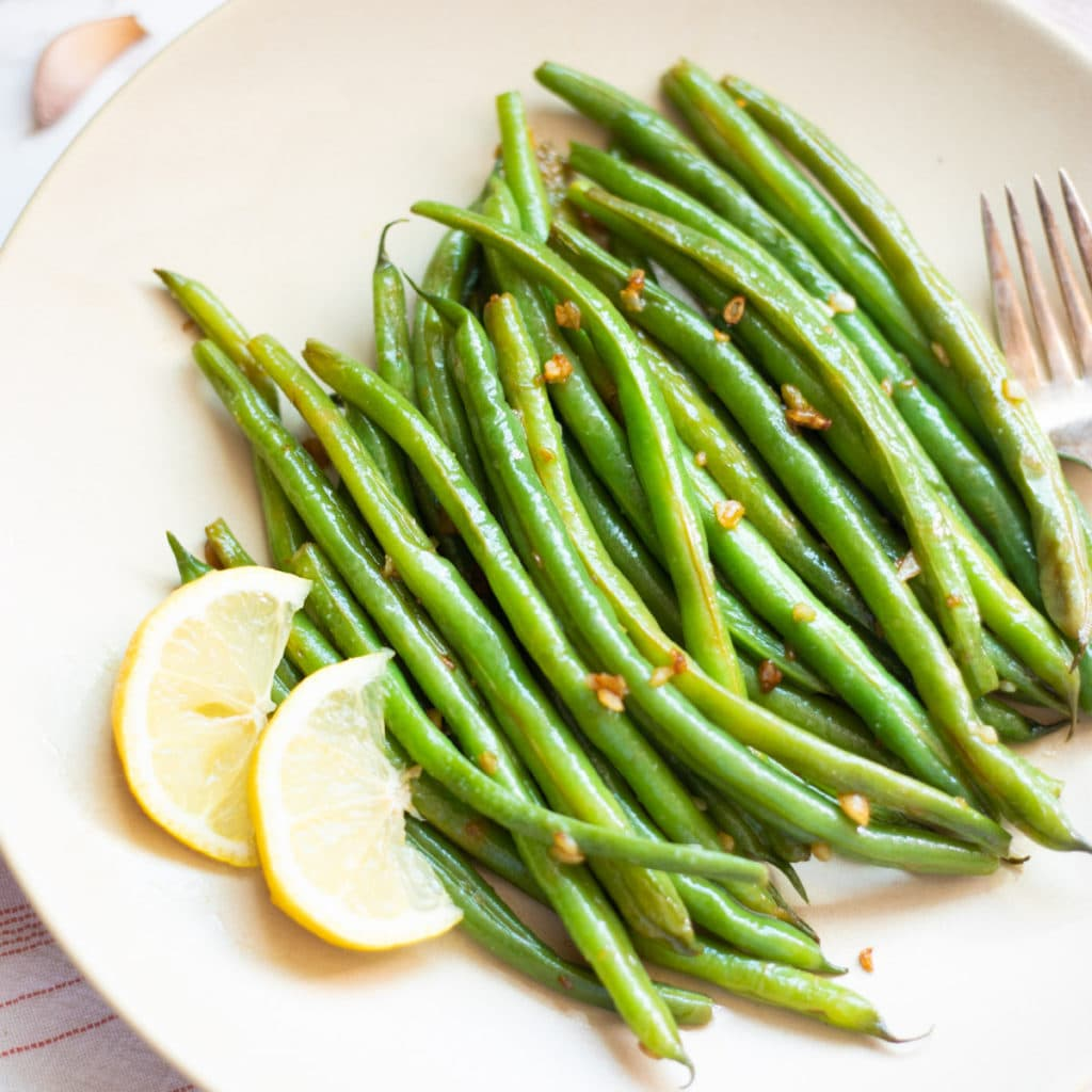 Steamed green beans with garlic and lemon on a platter