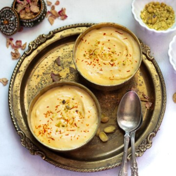indian mango dessert made with greek yogurt served in 2 pretty bowls