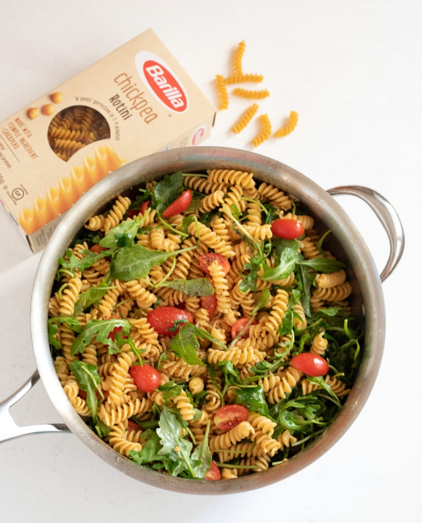 Rotini pasta with arugula and cherry tomatoes in a pan with a box of barilla chickpea pasta on the side