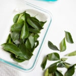 Curry leaves in a towel paper being stored in a pyrex box