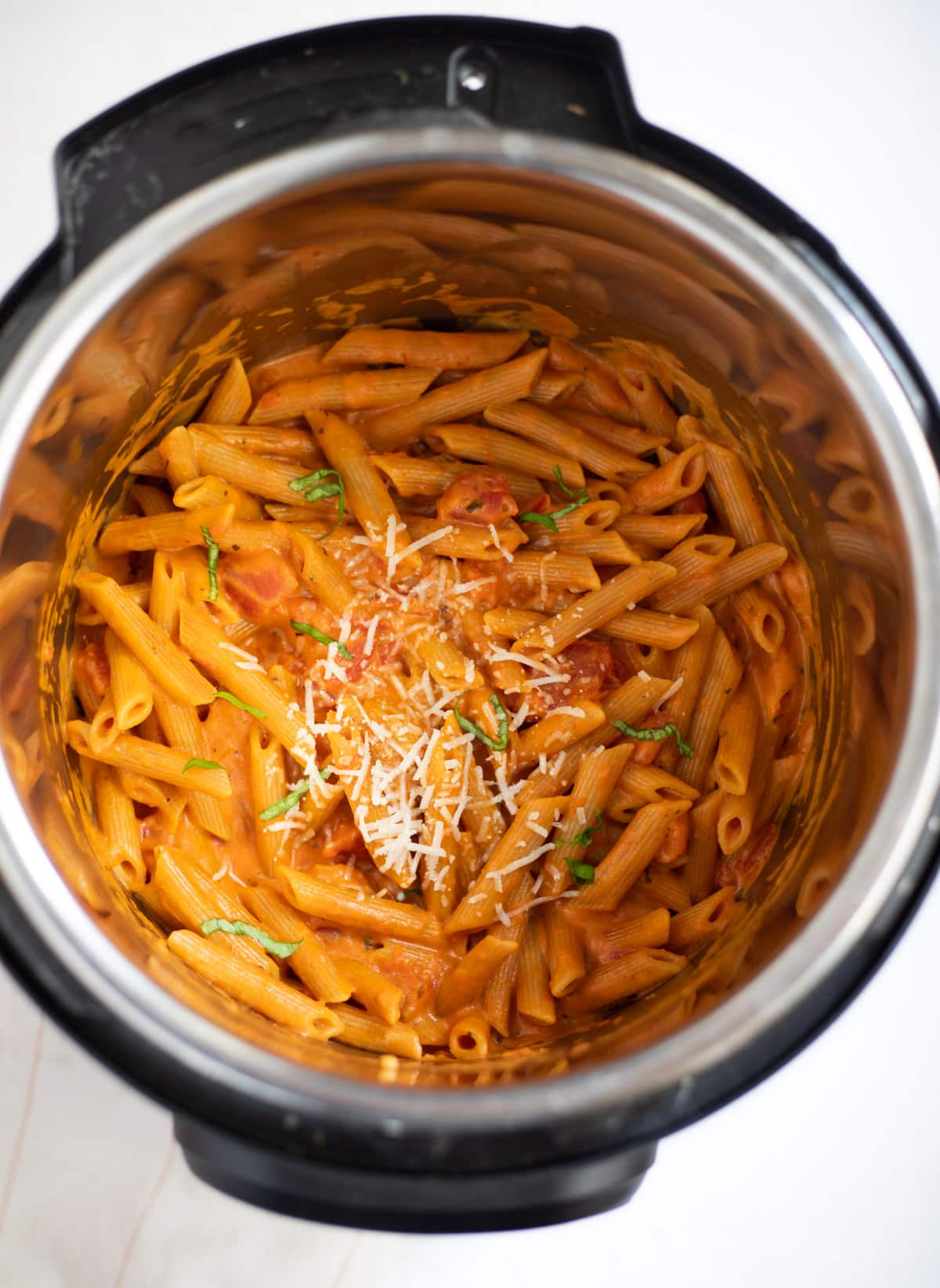 Instant pot Penne Pasta in Tomato Cream Sauce garnished with basil leaves and parmesan cheese