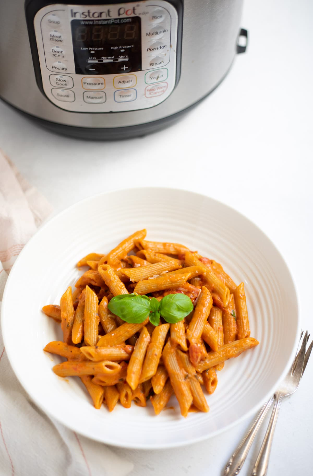 Penne Pasta in Tomato Cream Sauce in a white bowl placed in front of the Instant Pot
