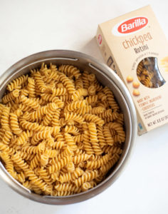 Cooked Rotini Pasta in a colander with a box of barilla chickpea pasta on the side
