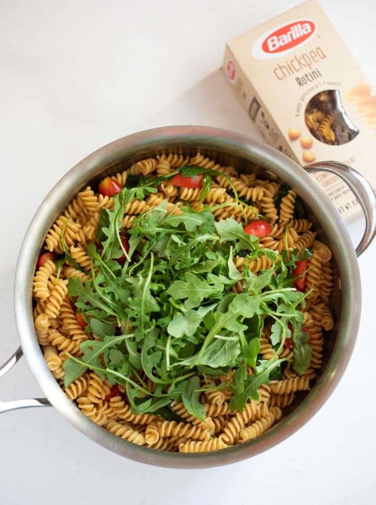 Rotini with cherry tomatoes and topped with baby arugula leaves in a large pan with barilla chickpea pasta box on the side