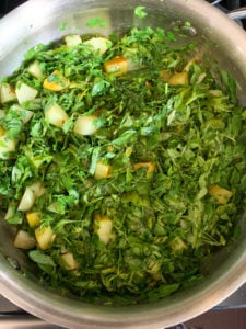 Potato and Methi Leaves being cooked in a pan