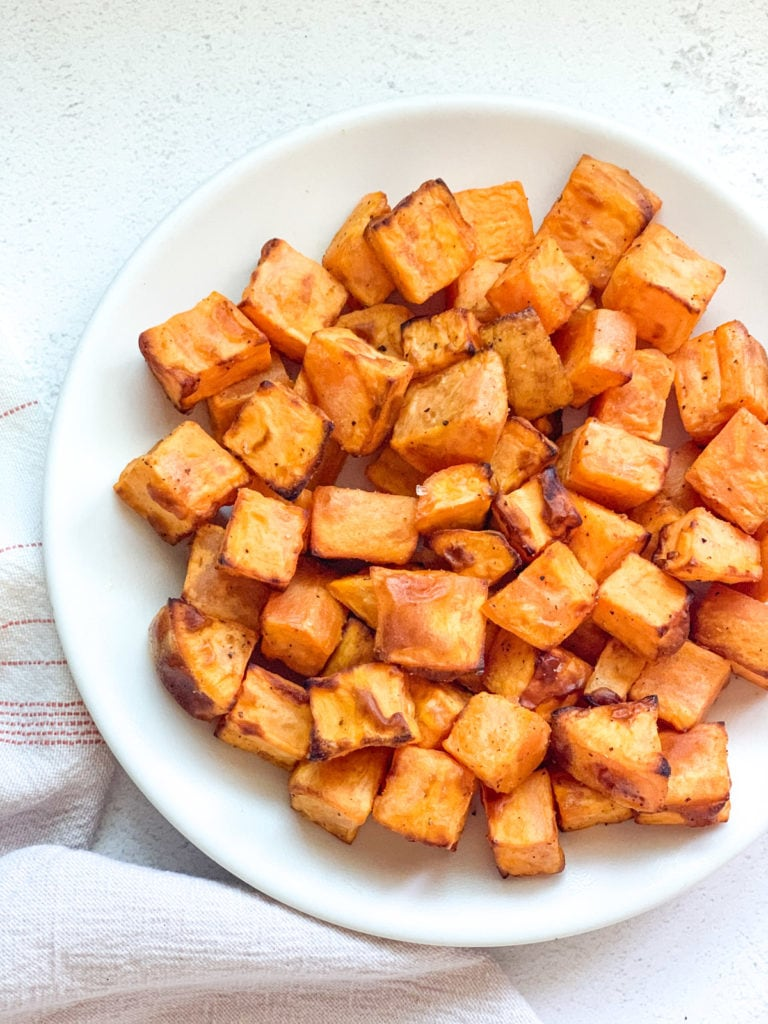 Roasted sweet potato pieces in a white plate