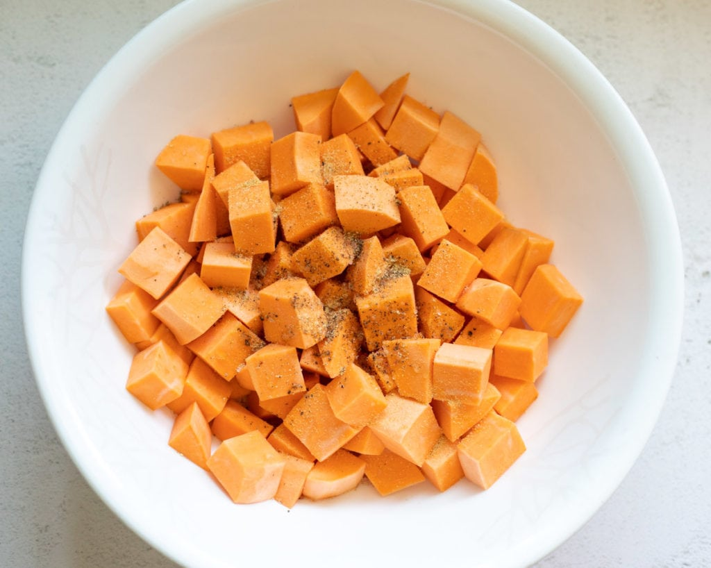 Spices and olive oil on sweet potato chunks