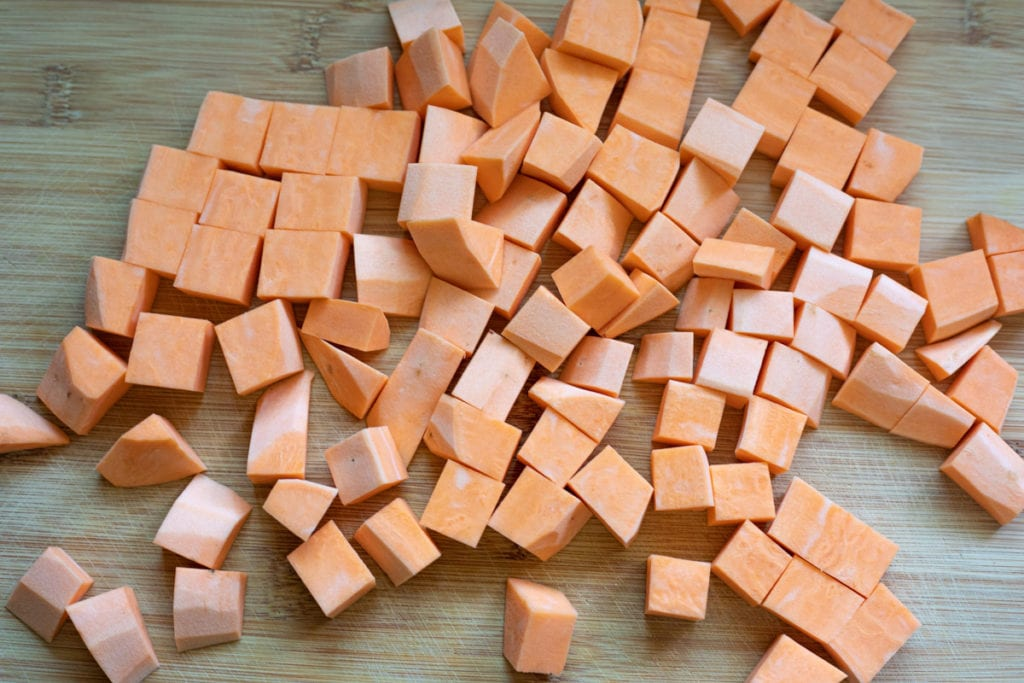 Sweet potatoes cut into cubes on a cutting board