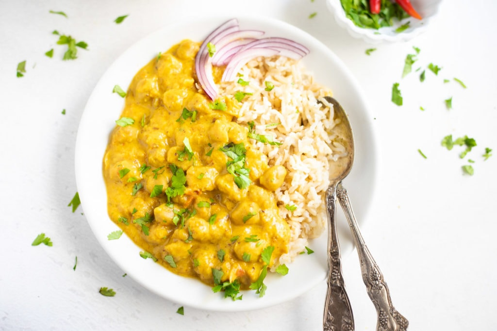 Chickpea Curry with coconut milk served over rice garnished with cilantro