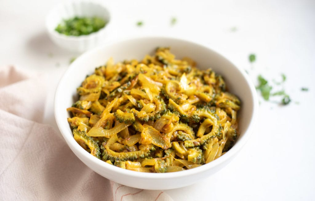 karela onion stir fry in a white bowl