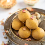 Homemade besan ladoo in a pretty silver plate with Diwali diya's in the back