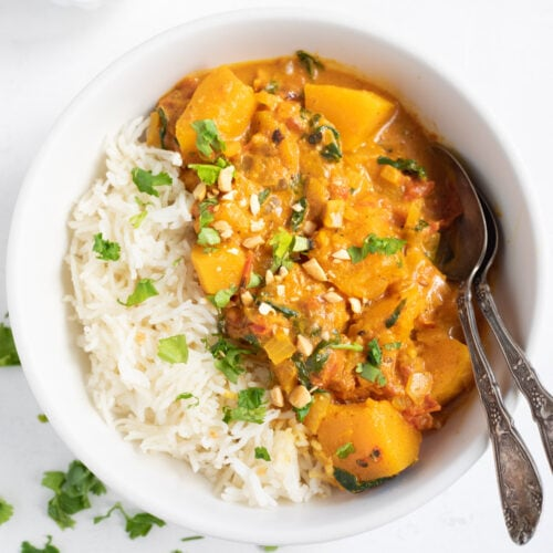 Butternut Squash Curry with spinach served over rice. Garnished with cilantro and peanuts