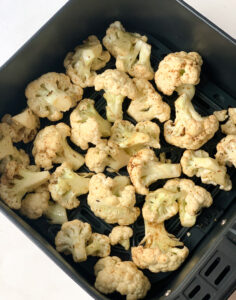 cauliflower mixed with oil and spices in an air fryer basket
