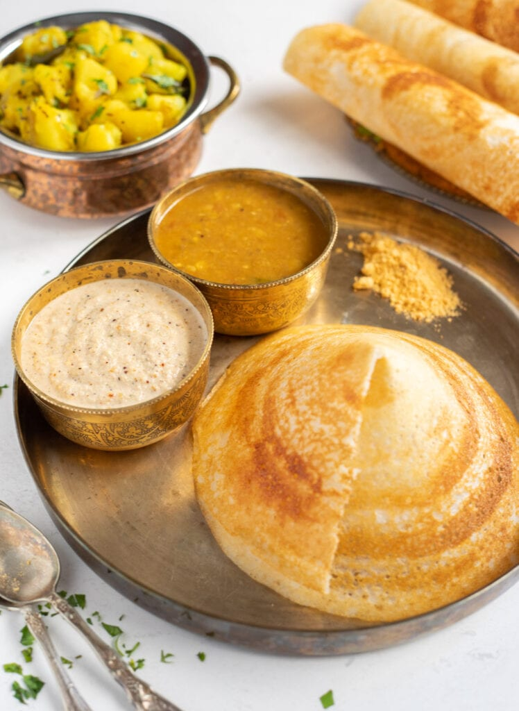 Cone shaped dosa with chutney, sambar and podi in a plate with potato masala on the side