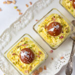 Gulab Jamun topped on shrikhand in a square bowl for serving indian fusion dessert