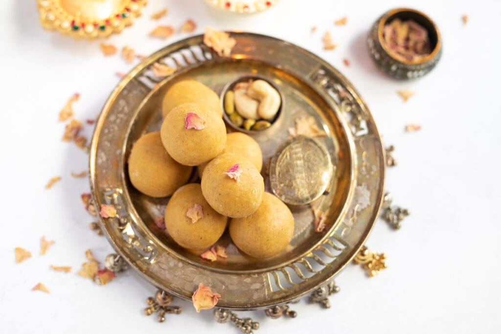 Besan Ladoo in a pretty plate topped with dried rose petals