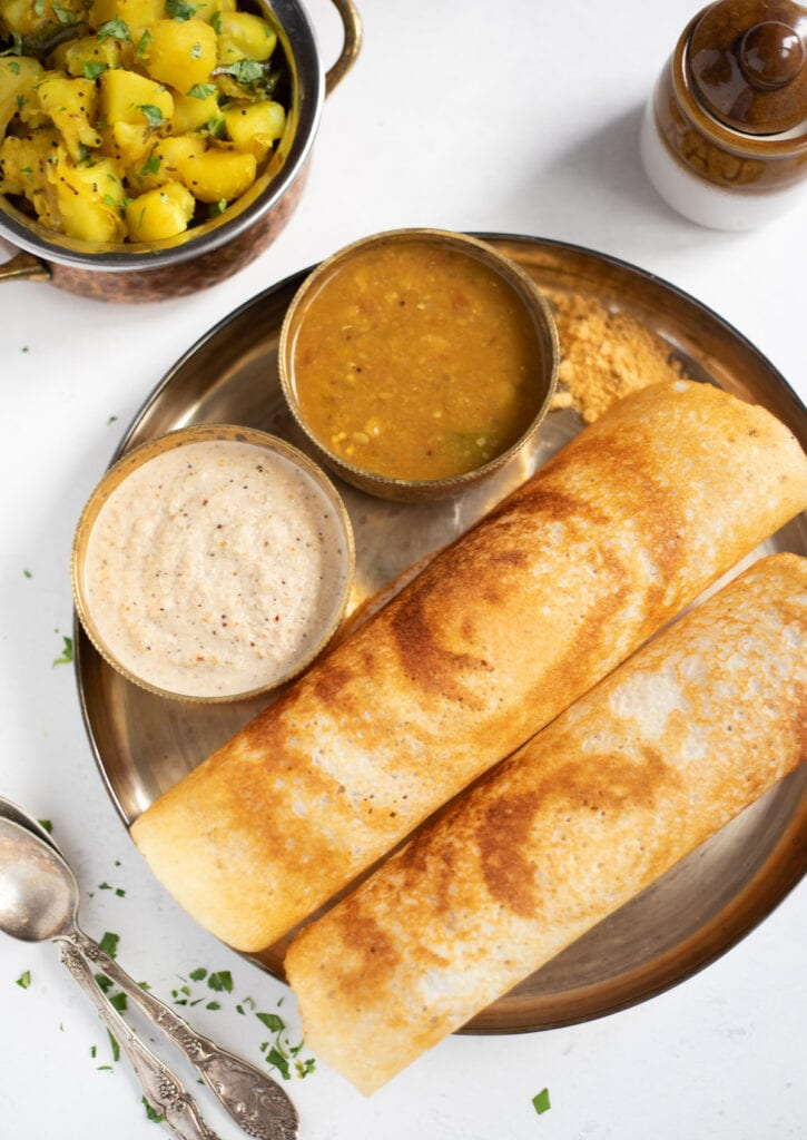Dosa with chutney and chutney, and potato masala on the side