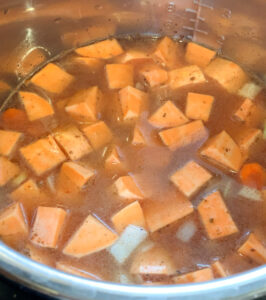 All ingredients in the pressure cooker for sweet potato soup