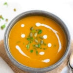 Sweet potato soup garnished with pepitas and cream in a bowl