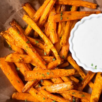 Roasted carrots on a brown paper with a dip