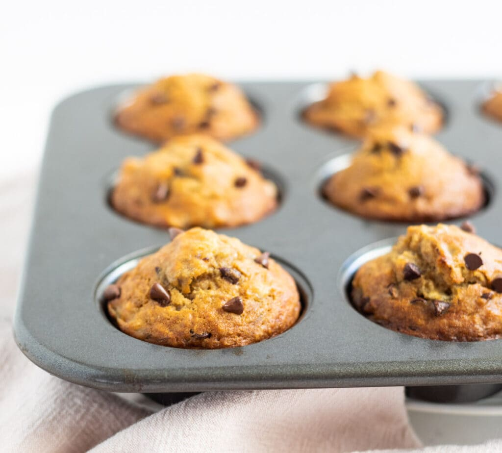 Muffins topped with chocolate chips in a muffin pan