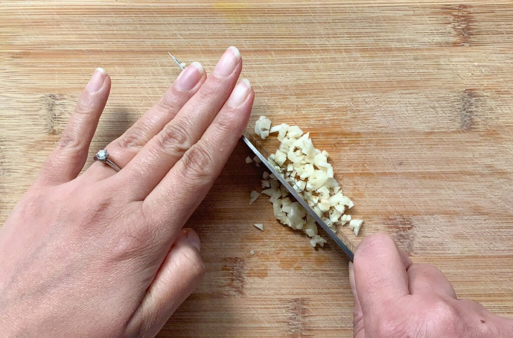mincing garlic using a knife