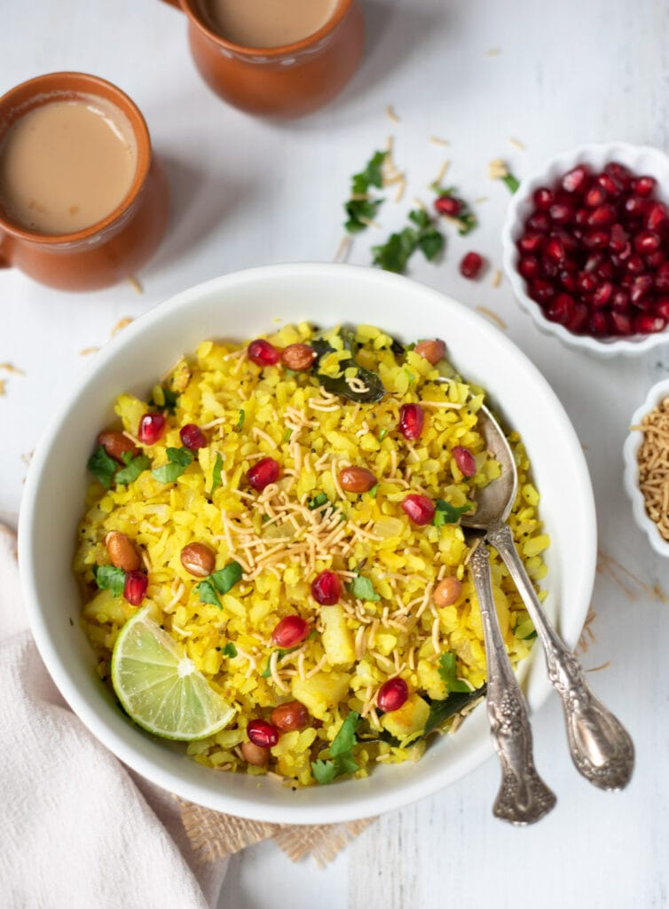 Poha garnished with peanuts and pomegranate in a white bowl with 2 cups of chai