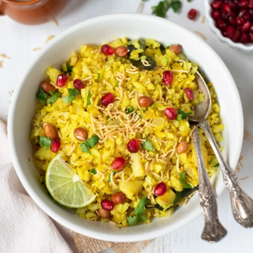 Poha garnished with lemon, sev, cilantro and pomegranate seeds