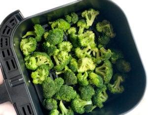 seasoned broccoli in air fryer basket