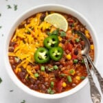 vegetarian quinoa chili topped with cheese, jalapeños and lime