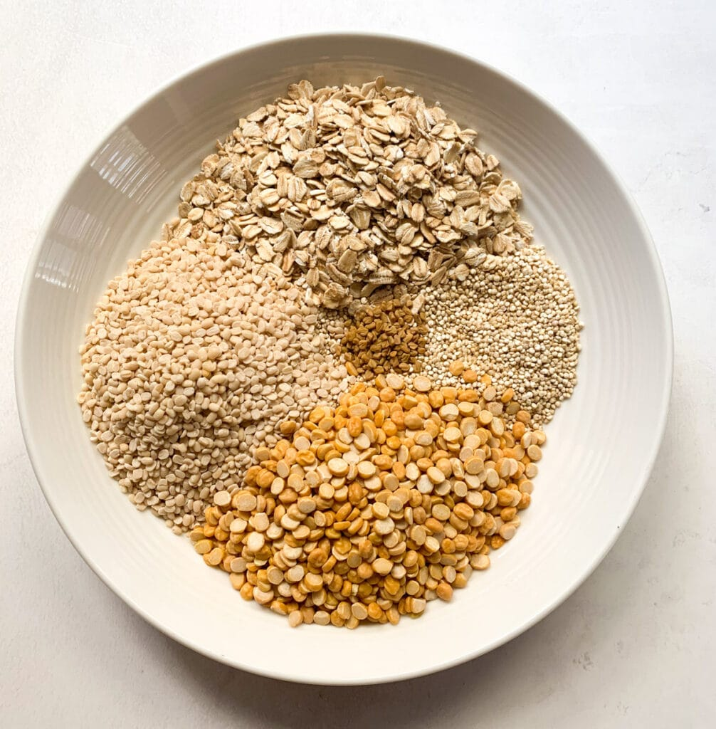 Quinoa, Urad Dal, Chana Dal, rolled oats and methi seeds in a bowl
