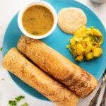 dosa with sambar, chutney and potato masala served In a blue plate