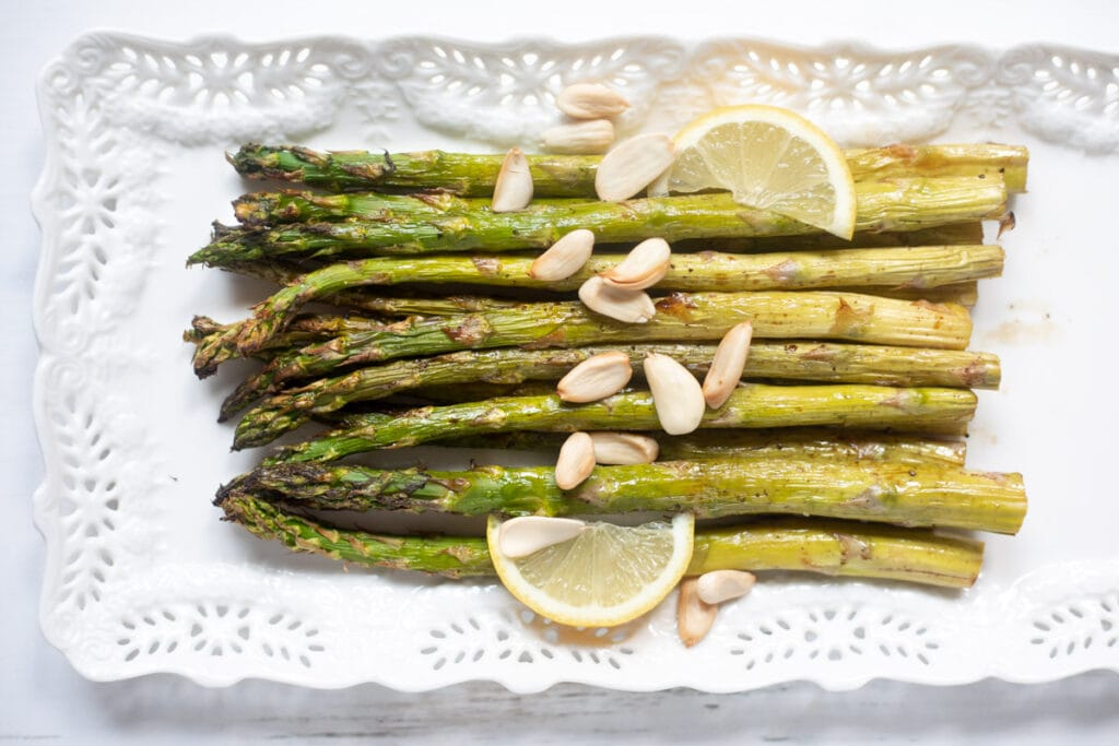roasted asparagus with lemon wedges and blanched almonds