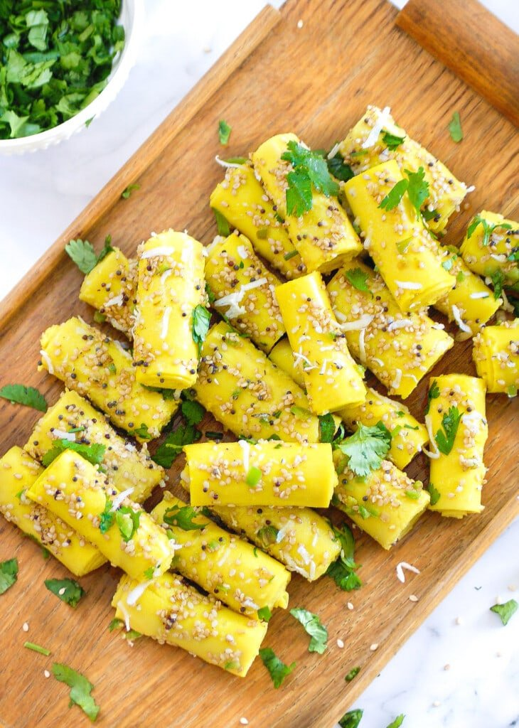 Khandvi on a wooden platter topped with a tempering of sesame seeds and garnished with cilantro