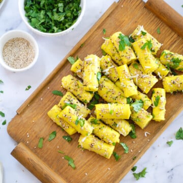 Gujarati Khandvi on a serving tray with sesame seeds and cilantro on the side