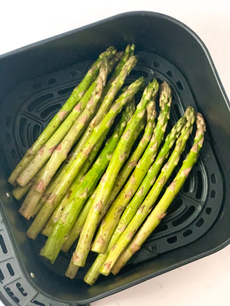 seasoned asparagus spears in the air fryer ready to be roasted