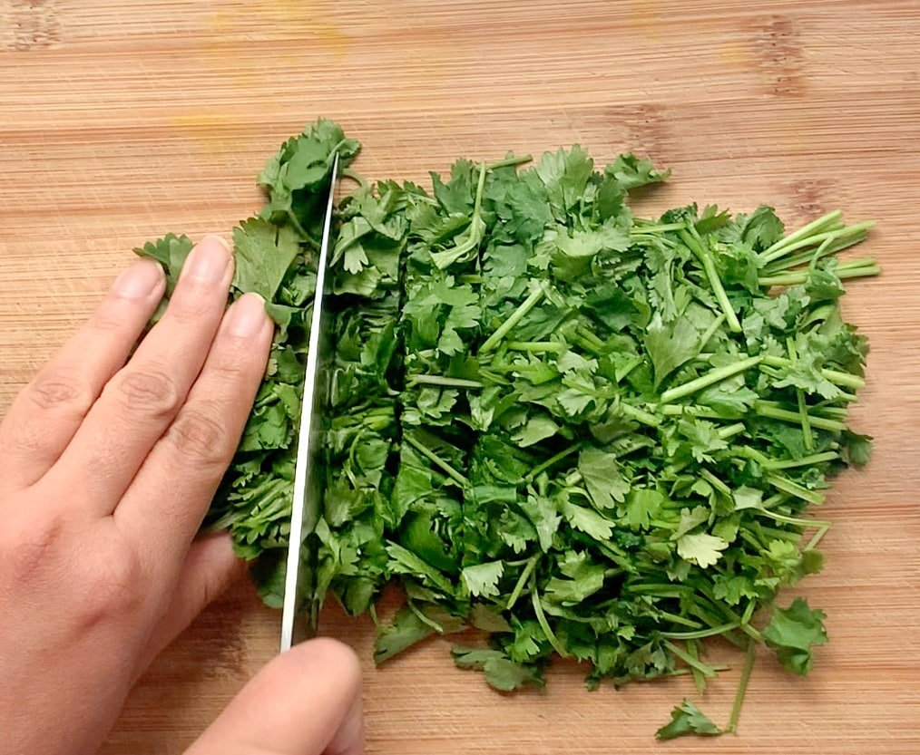 Cutting cilantro leaves with a sharp knife on a wooden cutting board
